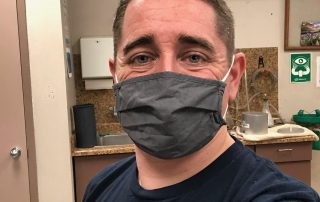 Portland member Andrew wearing a mask and a PROTEC17 t-shirt at work