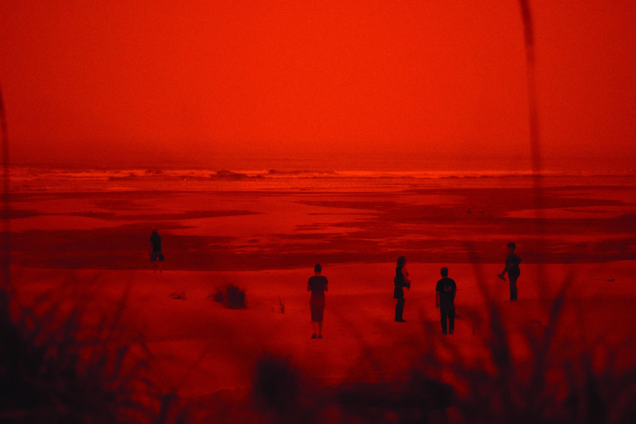 Photo of people at the Pacific Ocean with red skies during the 2020 wildfire season